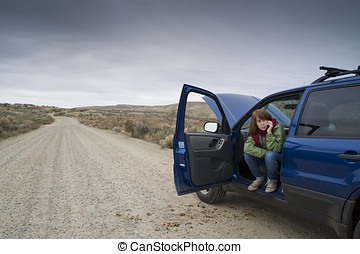 Teenage girl with a broken car - Teenage girl talking on a...