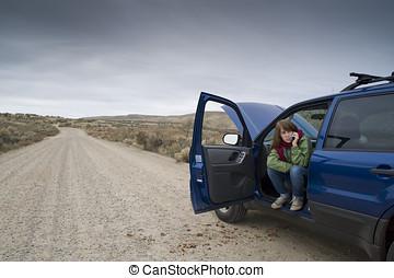 Teenage girl with a broken car - Teenage girl talking on a...