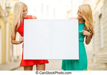 two happy blonde women with blank white board - summer...