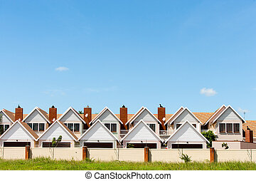Townhouses. - Residential fenced house complex against blue...