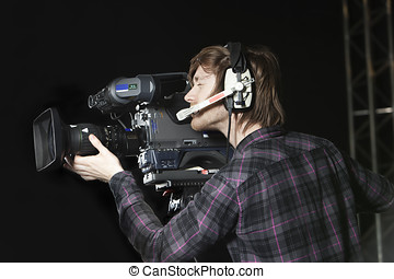 Man operating a TV Studio Camera - Young man operating a...
