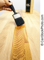 Brushing oil onto a wood surface - Brushing a protective oil...