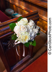 Wedding Bouquet on Pews - A bouquet of roses attached to a...