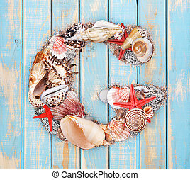 Letter G made of seashell on blue wooden background