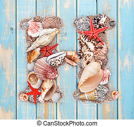 Letter H made of seashell on blue wooden background