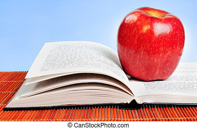 Open book and red apple