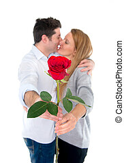 red rose with a couple kissing in the background