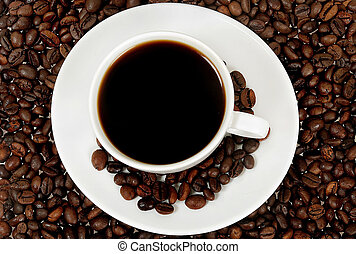 Cup of coffee on roasted beans