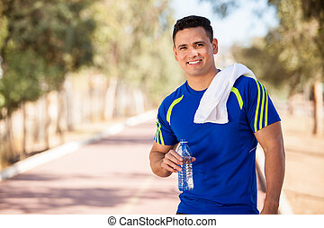 Happy young man drinking water - Young handsome athlete...