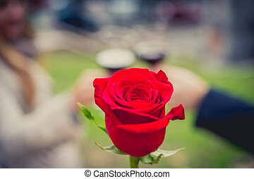 close up a single rose with a coule drinking wine