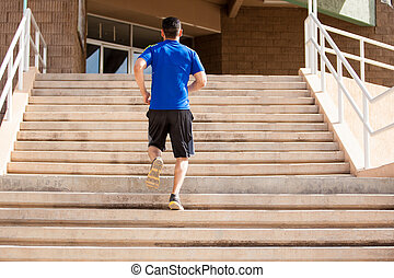 Exercising in a flight of stairs - Young man going up a...