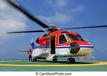 The offshore helicopter is landing to embark passenger at...