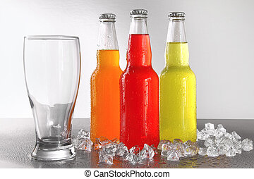Three bottles with drinks with glass and ice against silver...