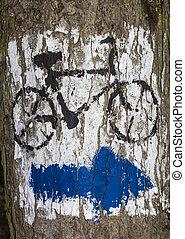 Blue arrow painted on tree bark