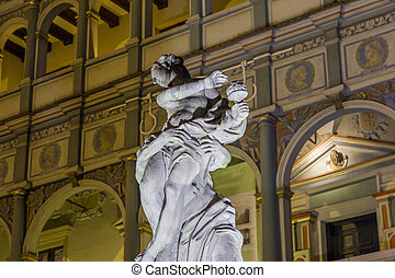 Night photo of historical fountain statue with beautifully decorated facade of the city hall in background, Poznan, Poland