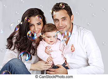 Family playing with soap bubbles - Portrait of cute arabic...