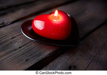 Flame of love - Image of red heart shaped candle burning on...