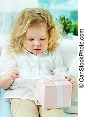 Unwrapping present - Close-up of a cute girl unwrapping her...