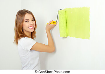 Beautiful girl painting a wall light background