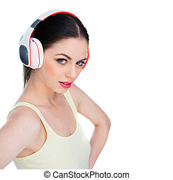 Attractive young woman wearing headphones as she listens to...