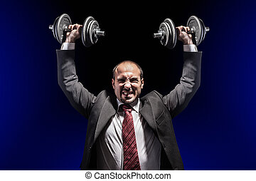 strength - a serious businessman wearing a suit and lifting...