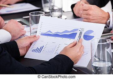 Businessman Holding Pen Over Graph In Business Meeting -...