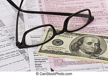 Tax Refund - Cash and eyeglasses on top of a US tax form...