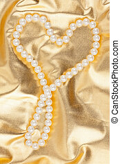 Symbolic heart on a gold fabric, as background