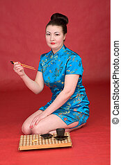 Japanese girl with sticks on the red background