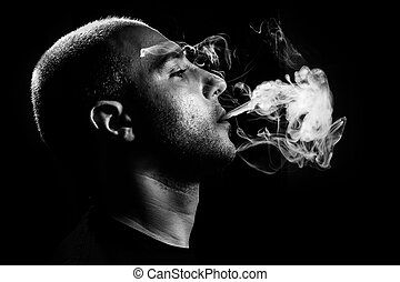 Smoking - dark and sullen shot of a young man smoking over a...