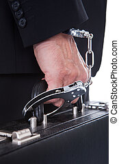 Hand With Handcuff Holding Suitcase - Close-up Of Person...