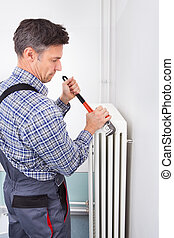 Plumber Fixing Radiator - Portrait Of Male Plumber Fixing...
