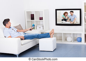 Man Watching Television - Mature Man Sitting On Couch...