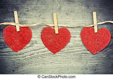 Three hearts hanging on a wooden boards background
