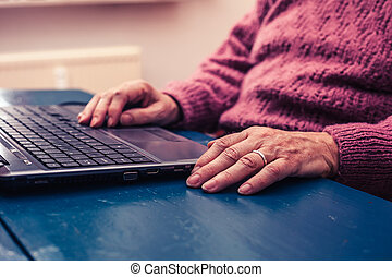 Old woman working on laptop computer at home