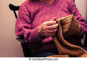 Old woman mending a jumper at home