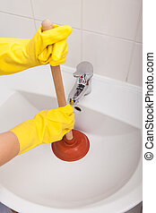 Person's Hand Pressing Plunger In Sink