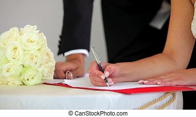 Couple signing their wedding register and smiling at camera