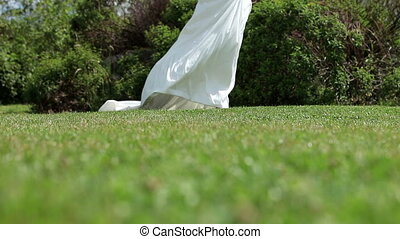 Bride in wedding dress walking on grass on a breezy day