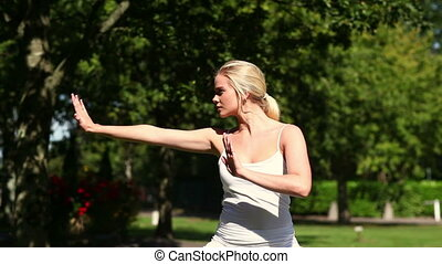 Pretty blonde woman doing tai chi in the park on a sunny day