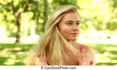 Pretty blonde relaxing in the park and smiling at the camera...
