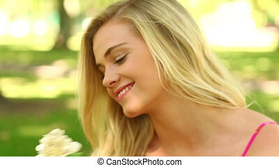 Pretty blonde relaxing in the park smiling at the camera...