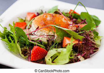 Warm goat cheese salad with melon and strawberries