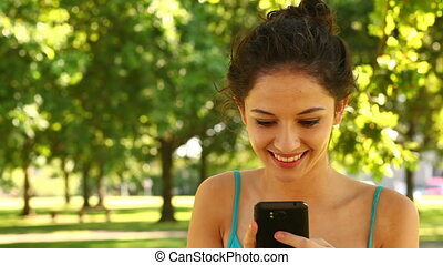 Gorgeous brunette sending a text in the park on a sunny day