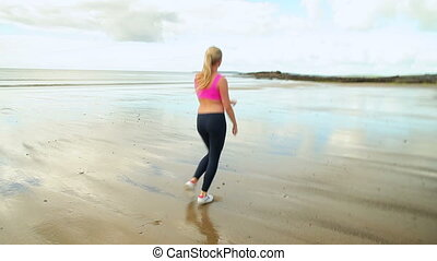 Fit blonde running on the beach on a clear day