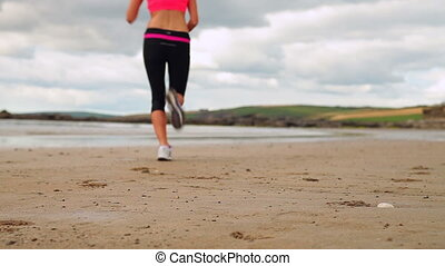 Athletic brunette running on the beach