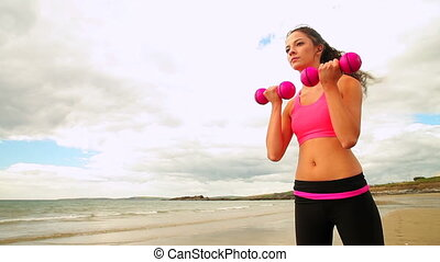 Beautiful brunette lifting dumbbells on the beach on a...