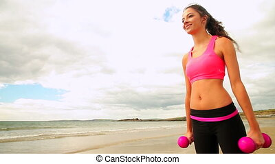 Smiling brunette lifting dumbbells on the beach on a cloudy...