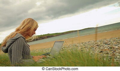 Pretty blonde using laptop by the beach on a cloudy day