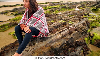 Pretty brunette wrapped in a blanket sitting by the beach on...
